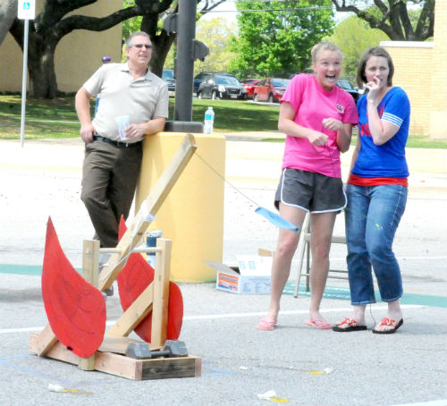 Trinity Valley Community College students Abby Baker (second from right) and Delores Stripling (far right) react as their egg flies across the parking lot during the 2nd Annual Earth Day Festival and Egg Catapult Competition on Tuesday. Their team, the Splat Squad, won third place and each received a $250 scholarship. TVCC biology instructor Brian Baumgartner is seen in the background at left. The competition, hosted by the TVCC Science Club, included students from TVCC and area high schools.
