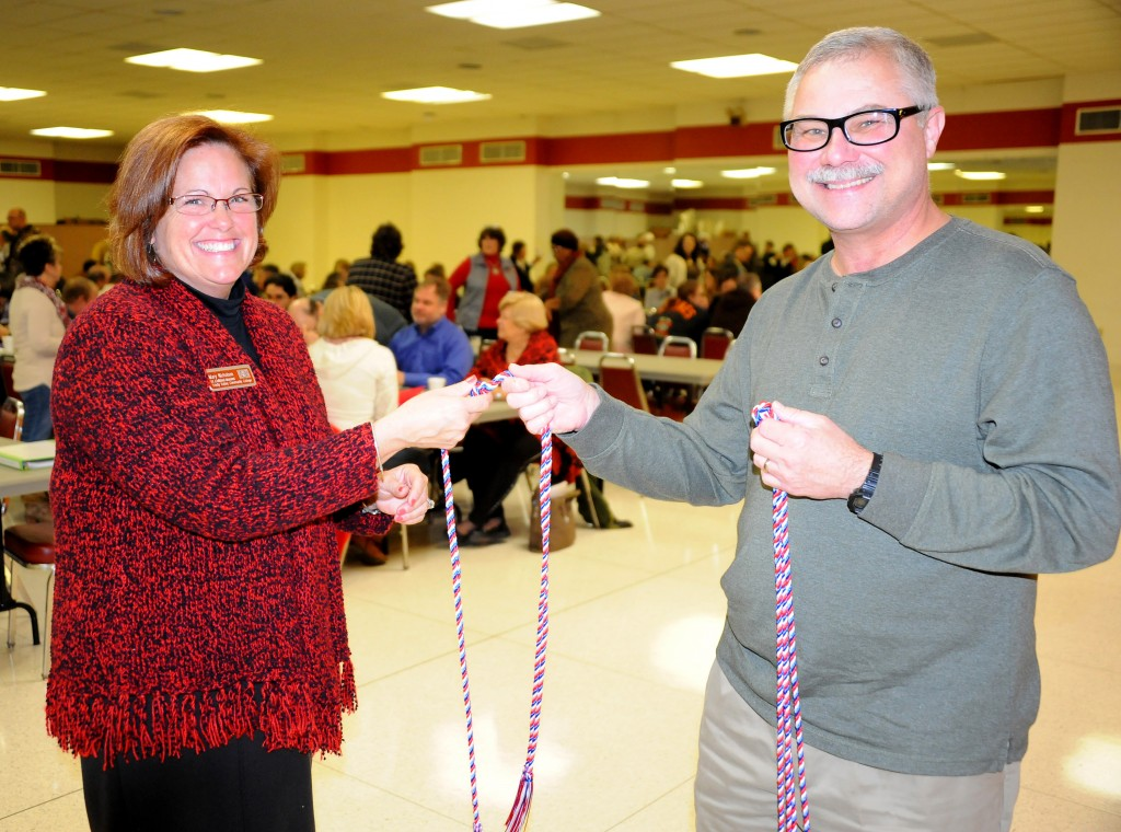 TVCC Vice President of Institutional Advancement Mary Nicholson (left) presents a red, white and blue military cord to faculty member Marshall Reeves during spring in-service Wednesday. Reeves and his wife, Iris (not pictured), each received a cord in recognition of their military service.